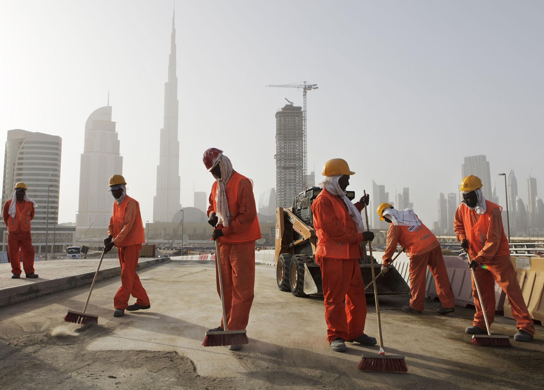 UNITED ARAB EMIRATES. 2012. Dubai.  With the world's tallest skyscraper Burj Khalifa in the background, Pakistani workers clean up a finished construction site on a road bridge in Business Bay area.   This story explores the world of guest workers in the arab Gulf oil states such as United Arab Emirates, Qatar and Kuwait. While marketing itself as a luxury playgrounds of tourism and business, close to 90% of UAE and Qatar's population are foreign workers.  Most of these workers come from far poorer nations such as India, Bangladesh, Philippines and Nepal, and the workers often endure very difficult employment and living conditions. Oftentimes parents will leave their home country for a decade or more to try to build up savings for their family back home, putting a big strain on family relations.   The World Bank estimates that yearly sum of remittances (the money being sent home by foreign guest workers) amounts to more than double all official foreign aid globally.